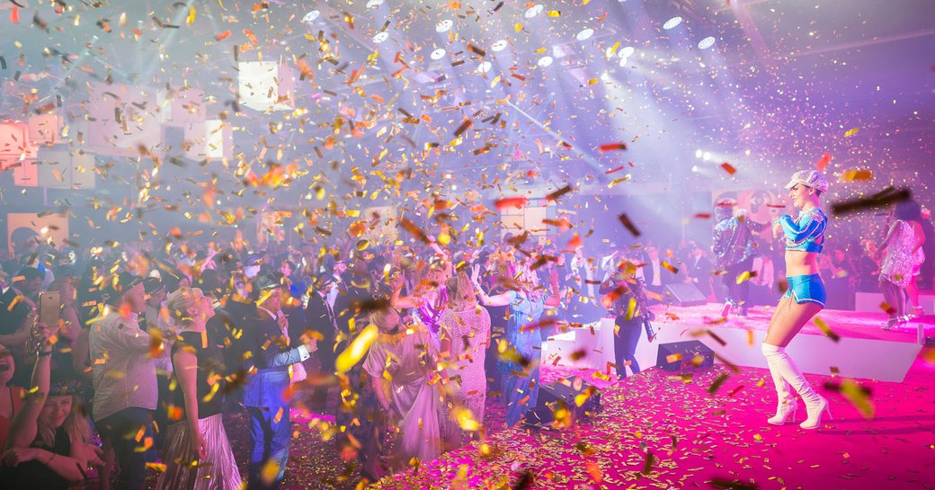 Female performer on stage in front of busy audience dancing, confetti falling all around