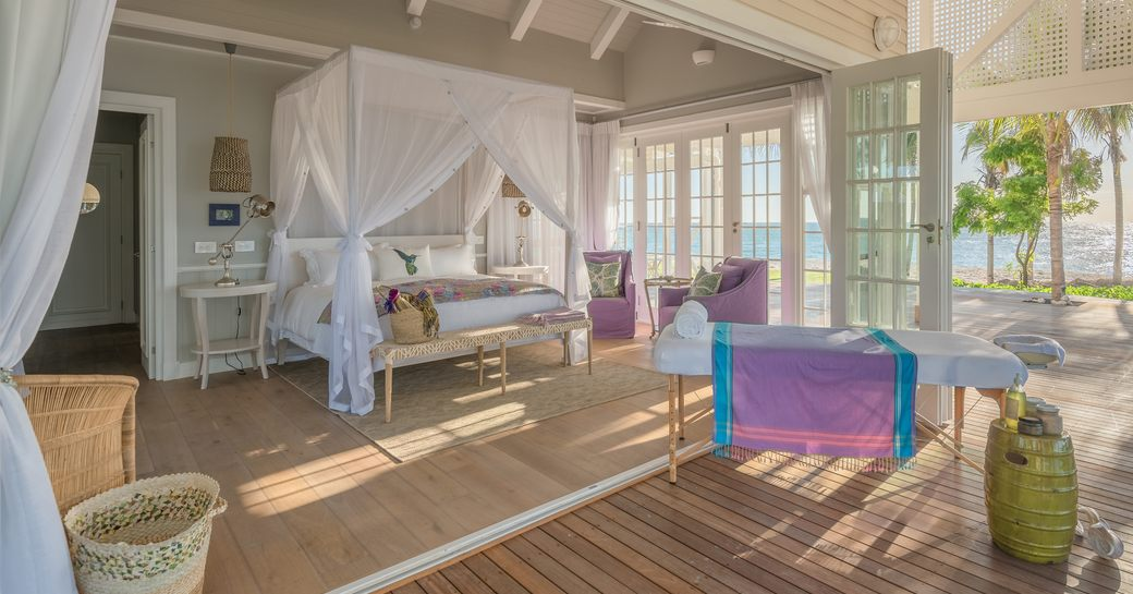 villa suite on thanda island, with doors to the terrace open and massage table set up