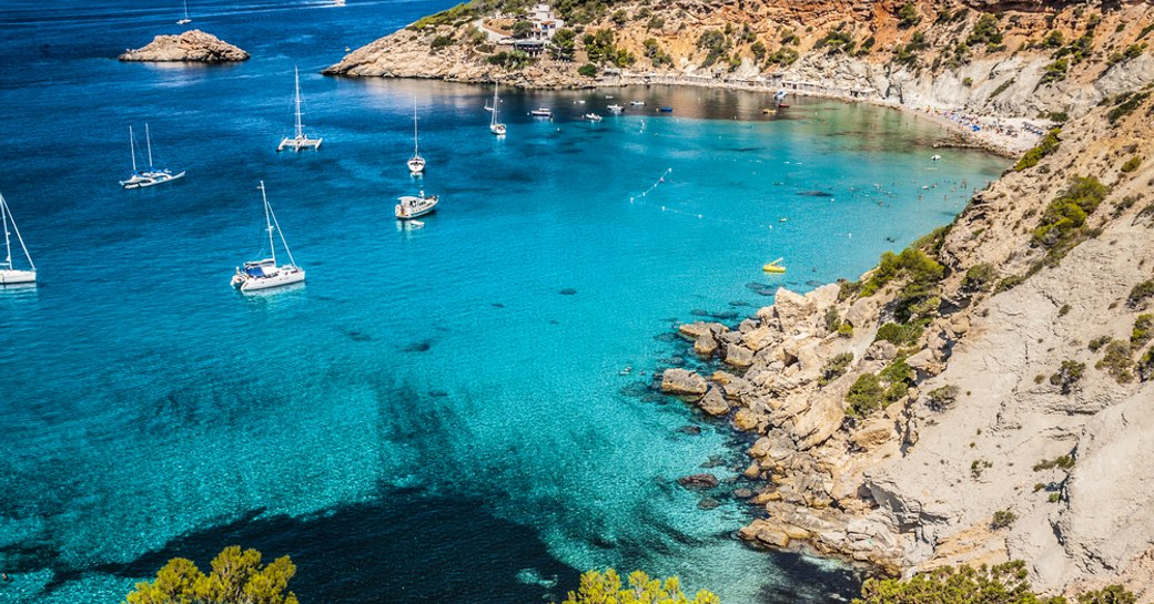 little blue bay in ibiza, with yachts on the water
