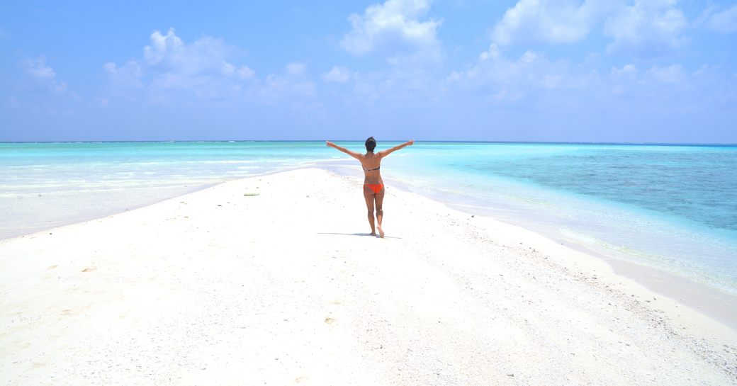 White sand bank in the Maldives with girl running on the sand