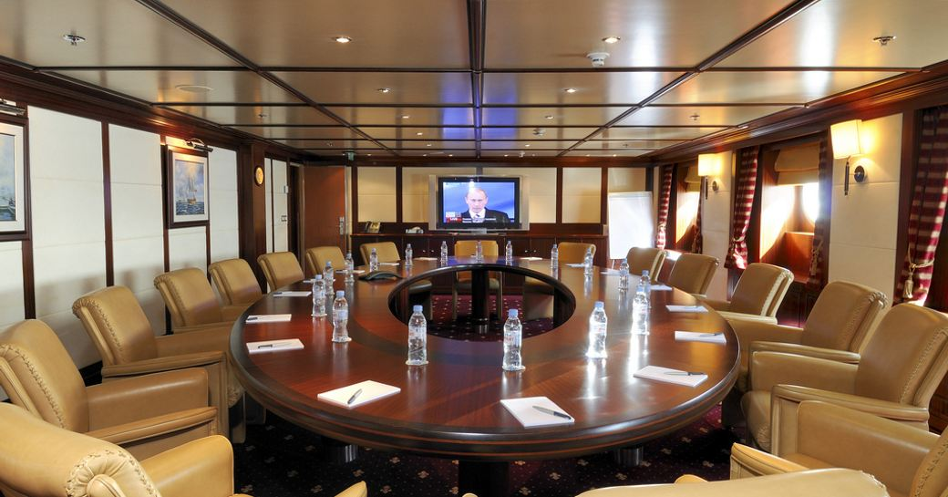 Conference room with water bottles and brown leather chairs on board charter yacht Lauren L