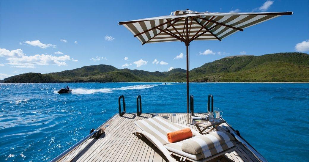 sun lounger lined up on reclining aft deck boarding platform aboard sailing yacht TIARA