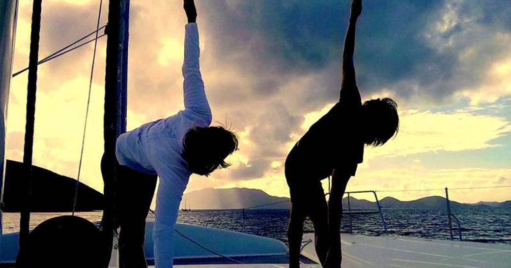 charter guests enjoy yoga on the deck