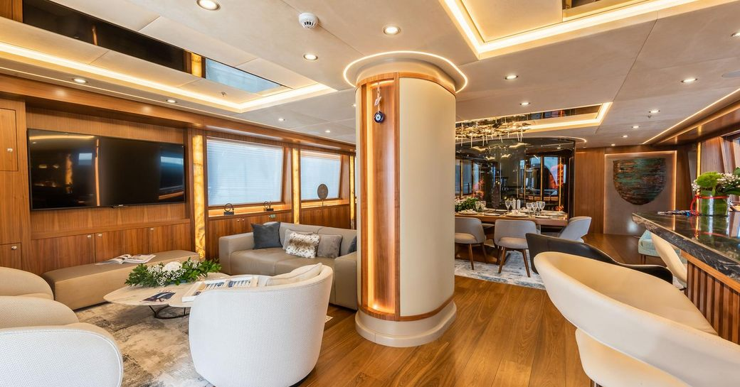 Main salon of sailing yacht ARESTEAS, with discreet lighting panels and warm wood with formal dining in background