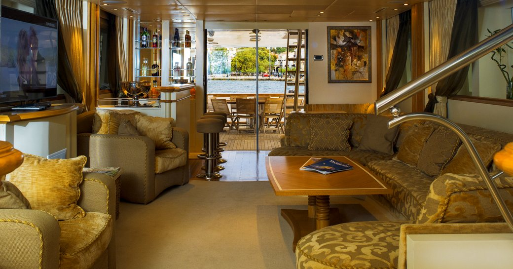 the plush and deluxe main salon of charter yacht carmen fontana with sofa, armchairs and state of the art entertainment system