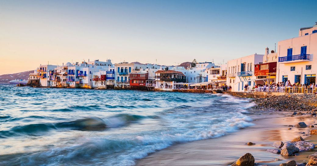 The sea hitting the shore of Mykonos, pastel buildings can be seen in the background