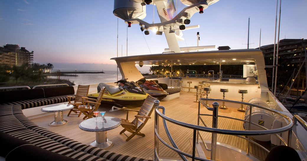 Superyacht sundeck, with cocktail tables and sofa seating, as well as two bars and Water-Ski storage