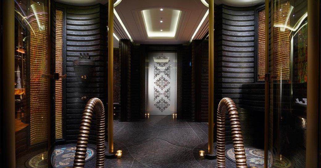 The black paneling and gold accents featured around the interior of superyacht KISMET