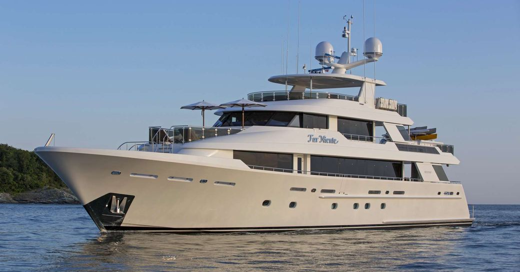 Luxury Far Niente relaxes at anchor in the blue Bahamian ocean on a yacht charter vacation