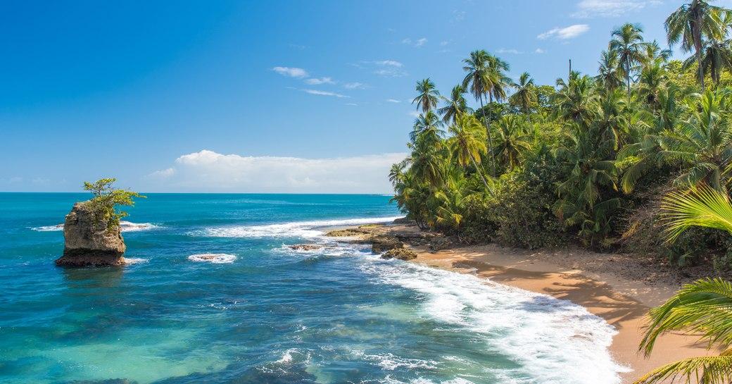 beach in costa rica with jungles and bright blue sea