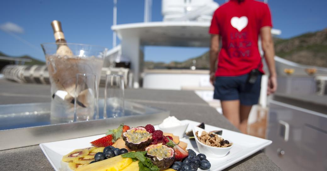 fruit plate being served of sundeck of luxury yacht