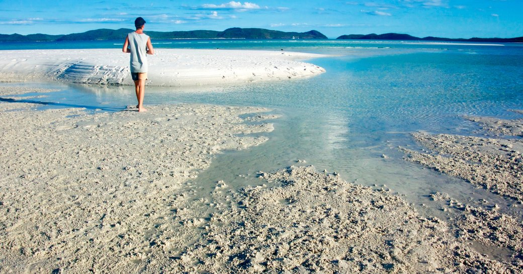 charter guests strolls along a beautiful white sand beach on the Whitsundays