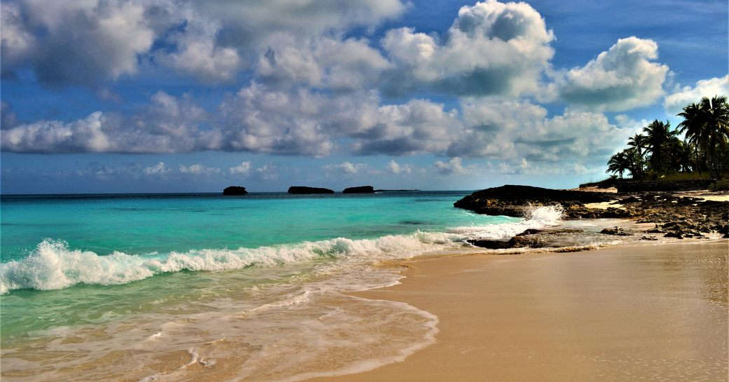Clear blue water lapping the sandy beach in the Exumas