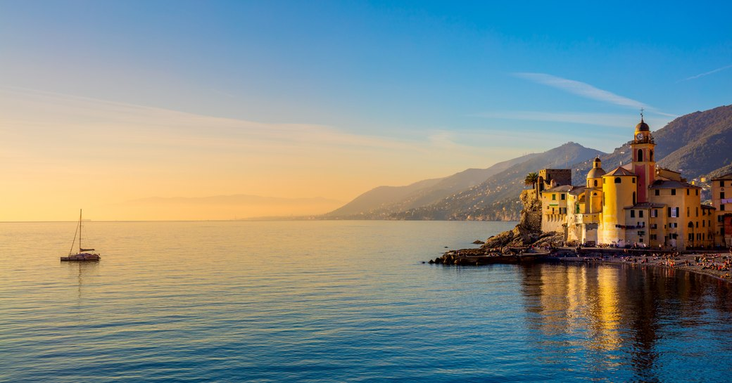 Mediterranean Sea at sunrise, small old town and yacht