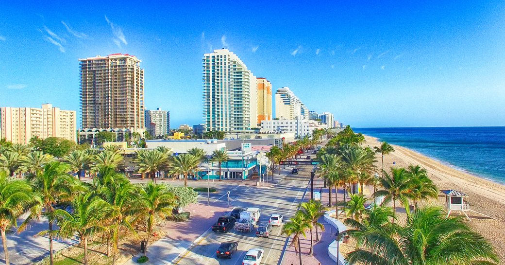 Overview of Fort Lauderdale coastline, towering hotels overlook busy road, sandy beach and sea to starboard.