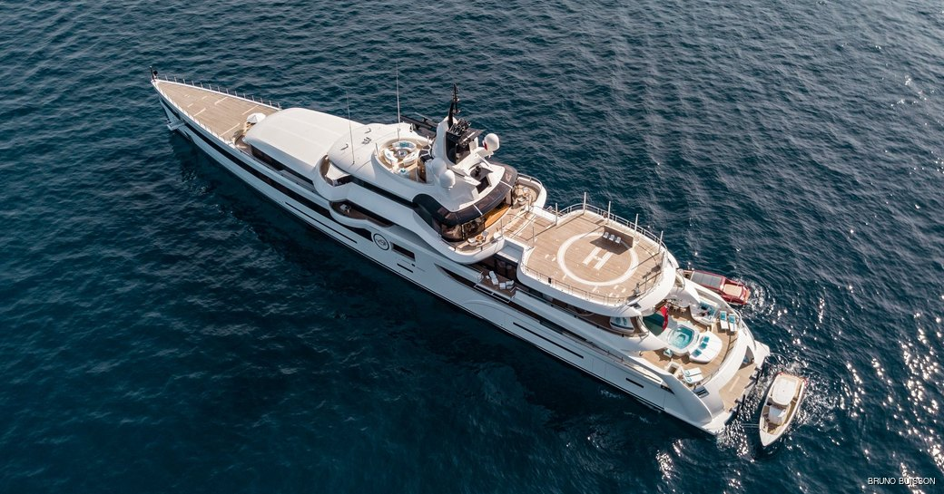 aerial shot os Feadship's Lady S as she elegantly cruises on her charter and also showing off her spacious sun deck, aft swimming pool, and hellipad