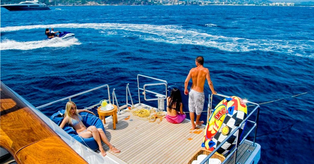 Couple on beach club of Illusion I yacht looking out at speedboat on sea