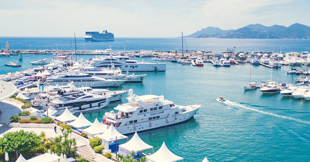 a fleet of superyachts in cannes getting ready to wow and impress many business people making deals