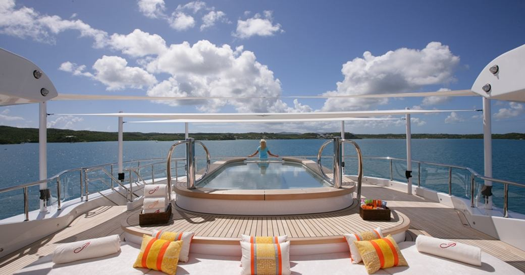 charter guest takes a dip in the pool on the sundeck of superyacht AMARYLLIS