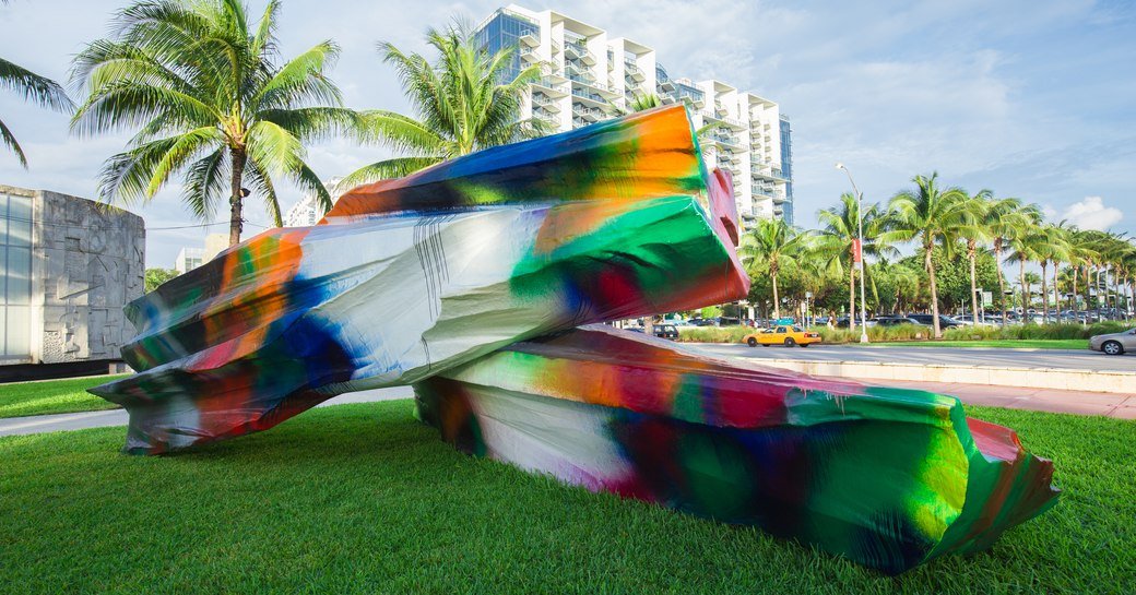 Sculpture on display during Art Basel Miami, rainbow colours shine out against green grass and towering Miami hotels in background.