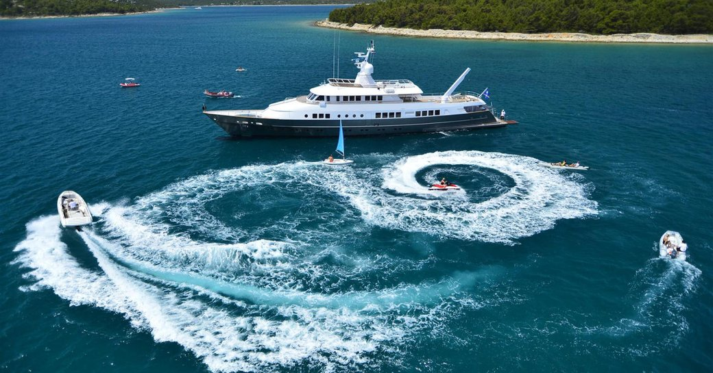 superyacht surrounded by blue sea and water toys