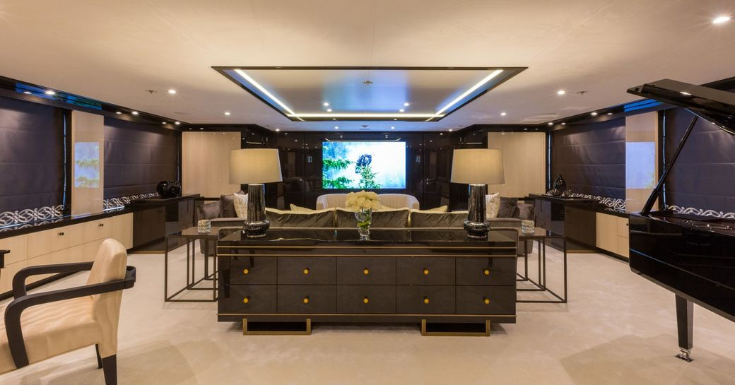 beautiful skylounge with cinema setup and grand piano on board superyacht ELIXIR