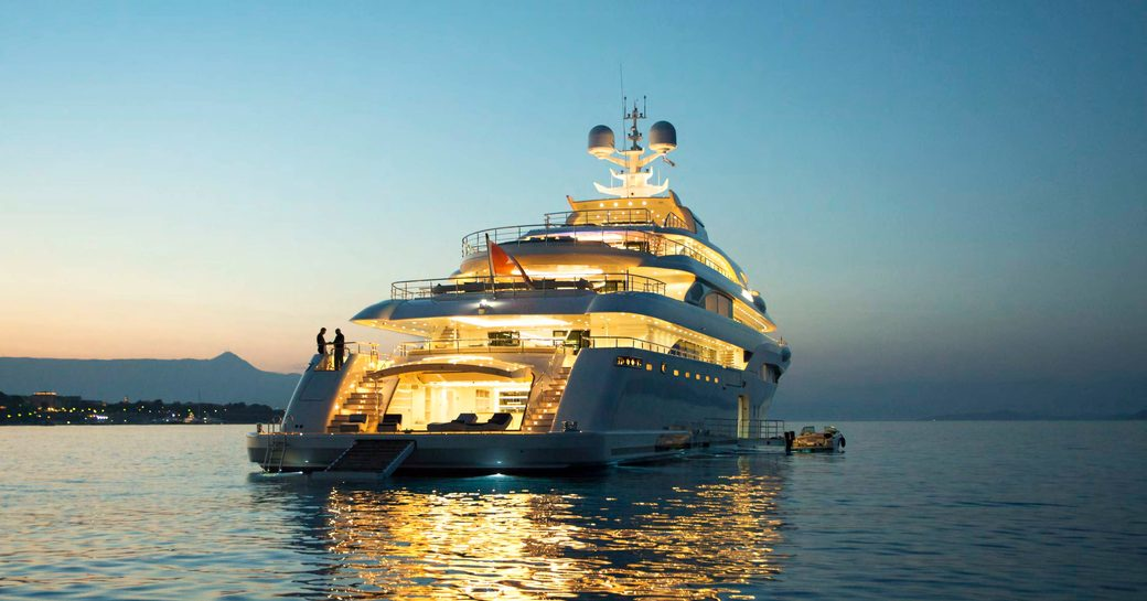 aft of superyacht O'PTASIA lit up at dusk while on a charter vacation