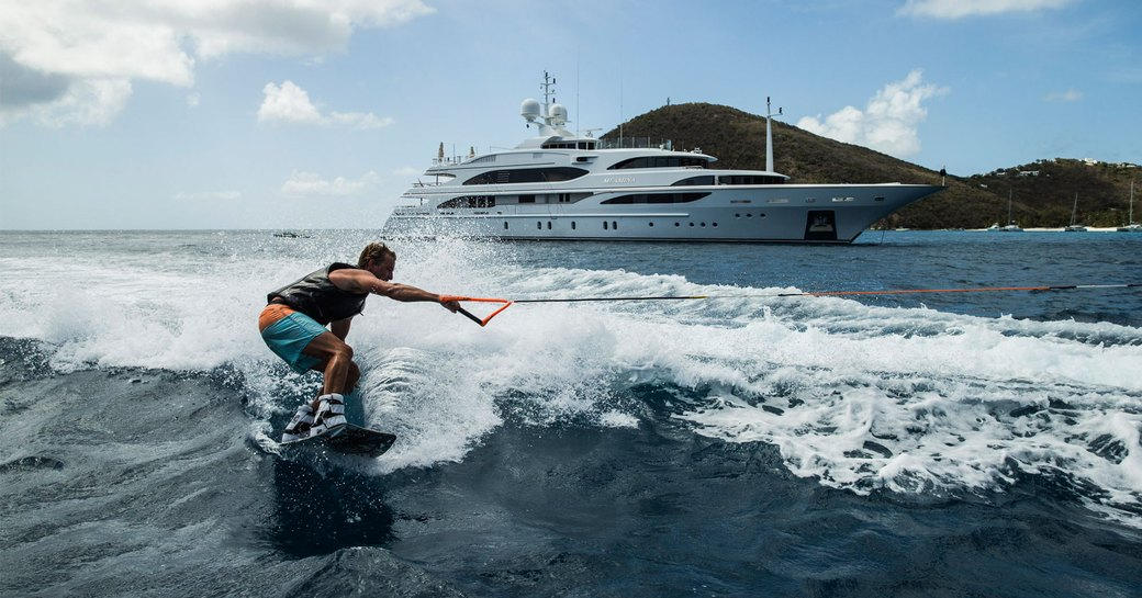 luxury yacht MEAMINA anchors as charter guest enjoys water toys