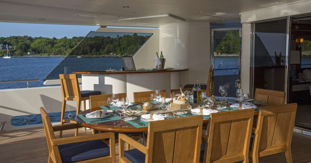 Alfresco dining set-up on superyacht Far Niente, with views over Bahamas in background