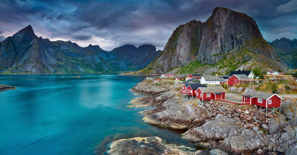 red houses perch on the water's edge in the Lofoten Islands, Norway