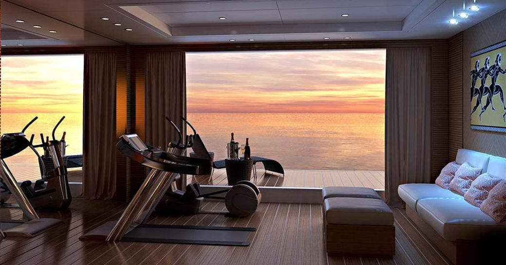 superyacht spectre beach club from inside, looking out over sunset on the water. gym equipment lined up and comfortable seating, with drinks on table outside