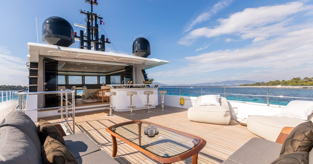 expansive flybridge with seating areas and bar on board superyacht ONEWORLD