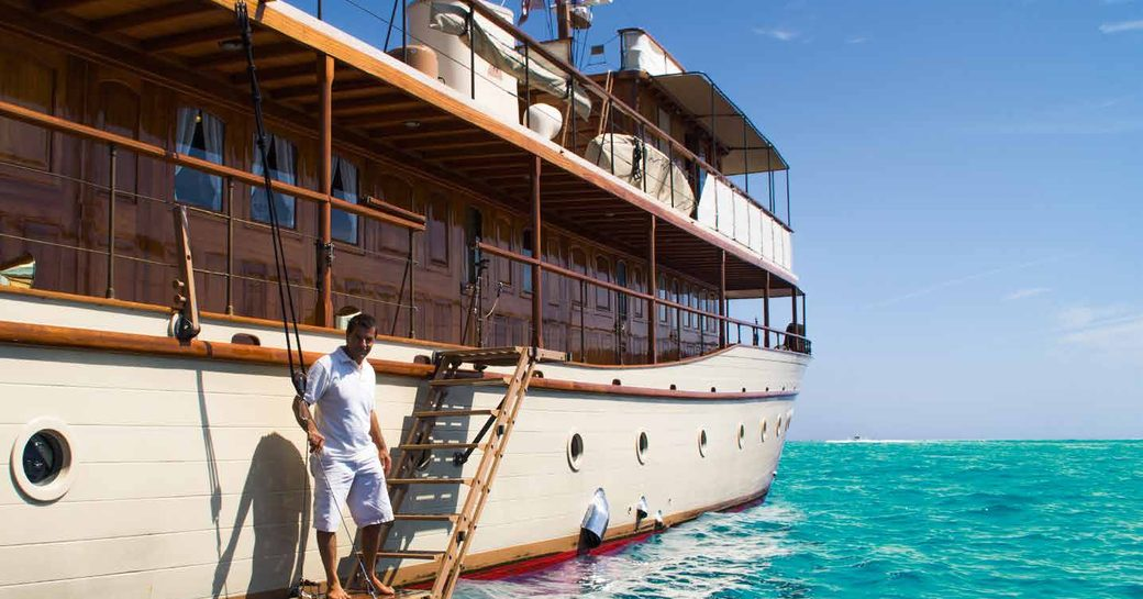 crew greets guests stepping on board luxury motor yacht over the rainbow