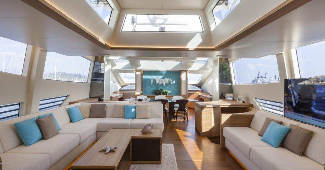 Light filled interior with tables and comfortable sofas on superyacht 55 FIFTYFIVE