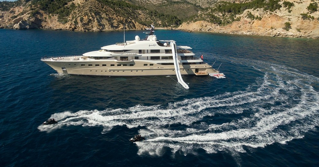 A superyacht with an inflatable slide attached and nearby Jetskis