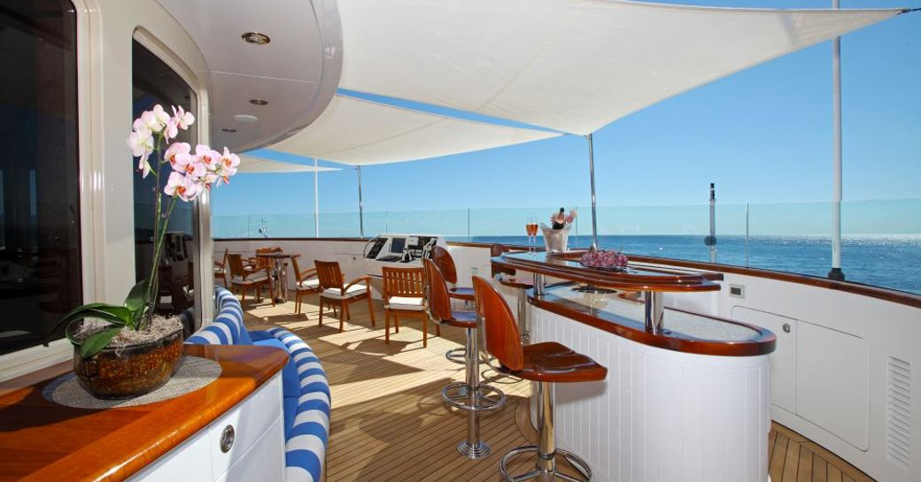Chairs line a bar beneath shading located on the exterior of a superyacht