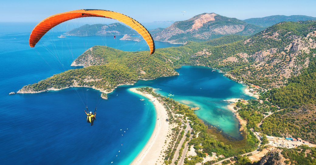 a guest on a luxury yacht charter who has anchored in oludeniz is paragliding over the breathtaking blue lagoon in turkey