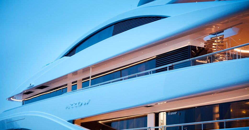 side profile of superyacht arrow as night falls, name plate on side of yacht visible