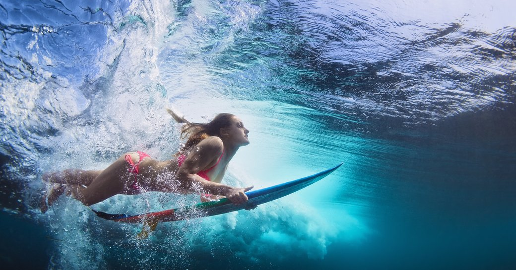 female surfer on board under the water