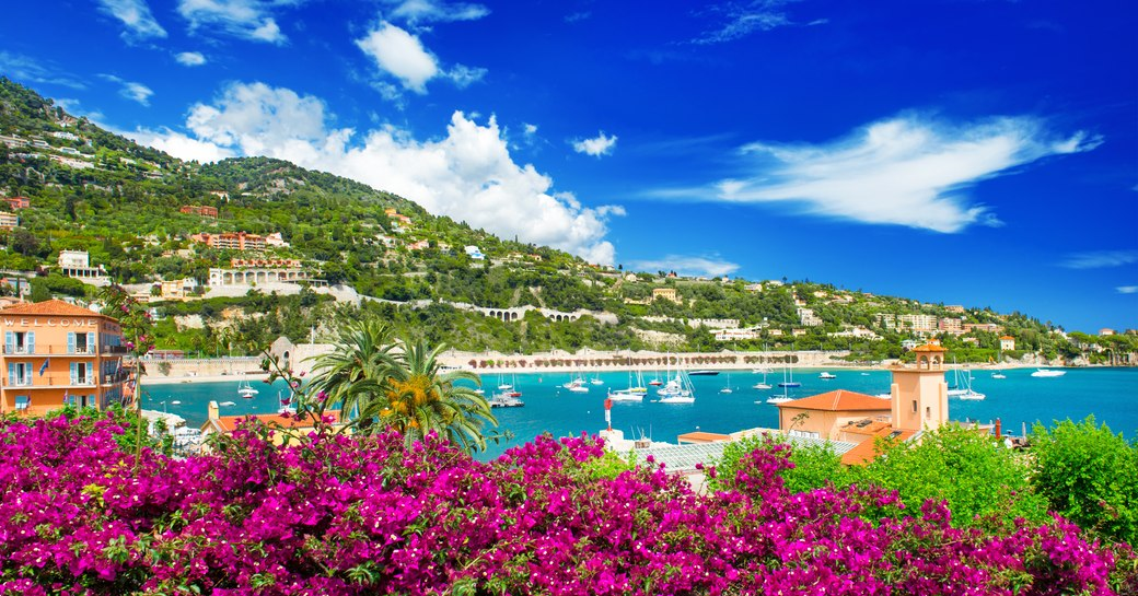 french-curved-coastline-against-blue-sea-dotted-with-yachts