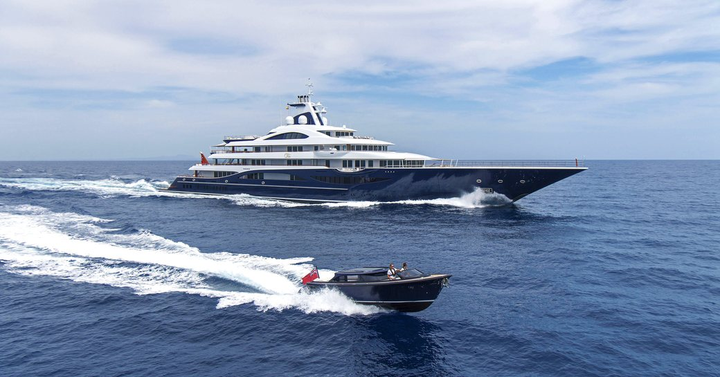 motor yacht Tis cruising the waters on her charter with her onboard tender cruising right beside her