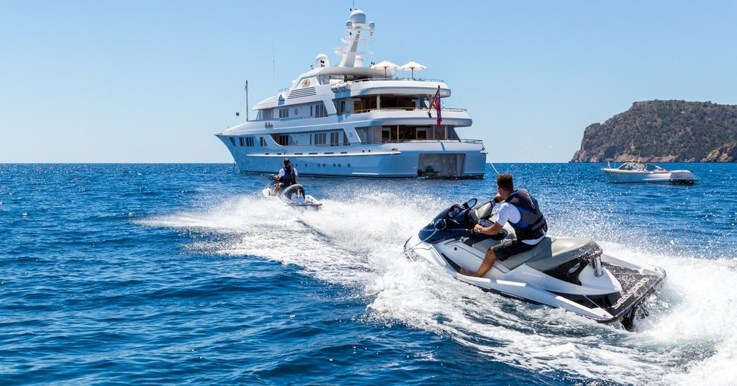 superyacht CALLISTO anchors in the Caribbean as charter guests play on the jet skis
