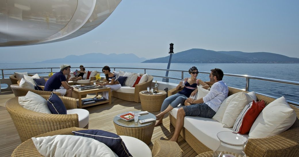 Guests on outdoor seating on deck of O'MEGA superyacht socialising
