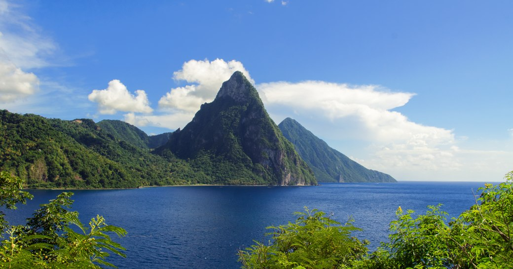a high and evergreen mountain in anigua surrounded by nature and water perfect for charter yachts to cruise in