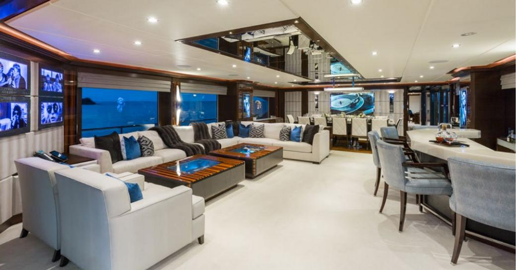 plush main salon with large lounge, bar and dining area, and rock 'n' roll photography collection aboard motor yacht 'King Baby'