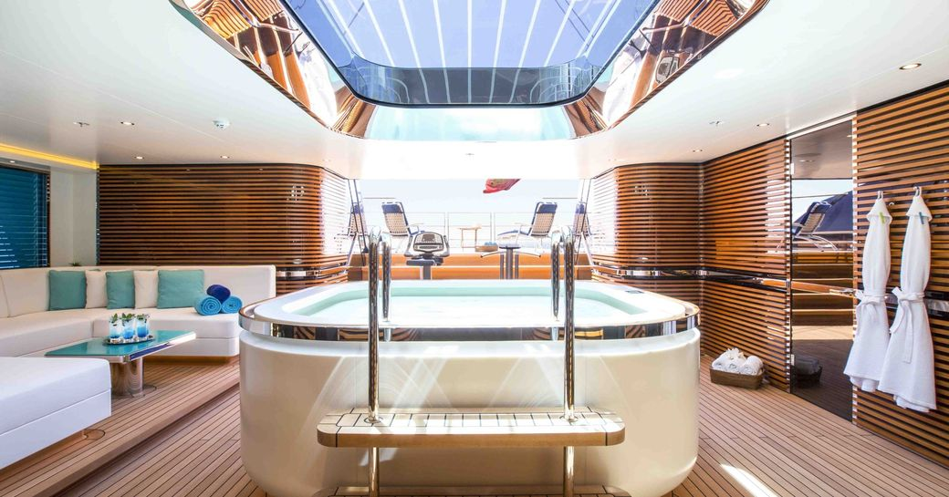 beach club of sailing yacht aquijo, with jacuzzi below glass ceiling panels and access to swim platform in background