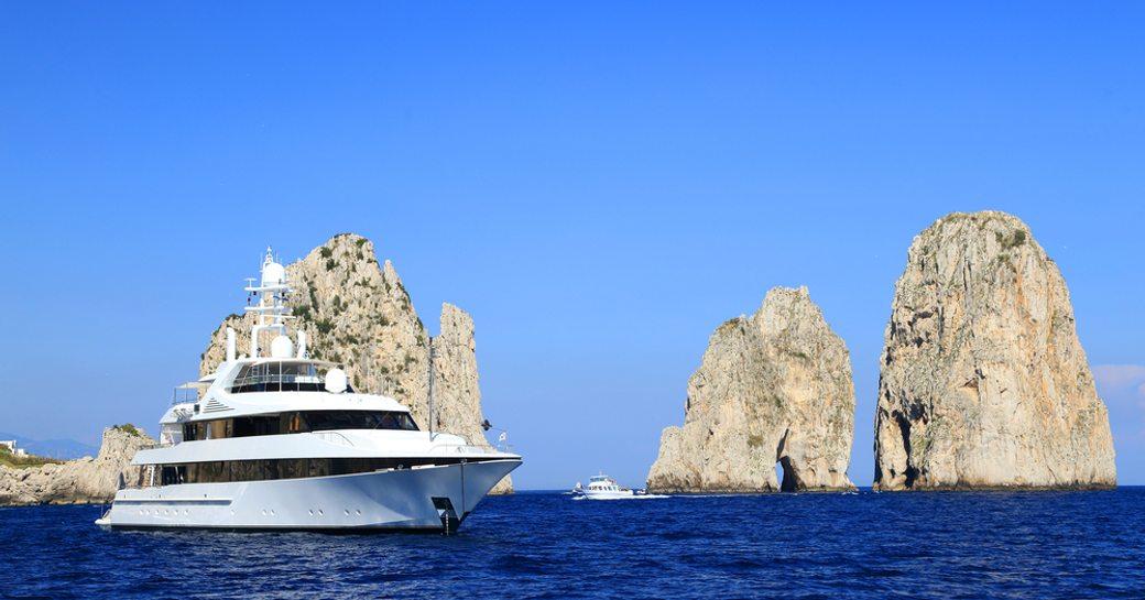 superyacht cruises in capri next to faraglioni rocks