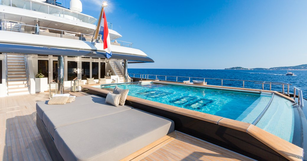 sunny day casting warm rays over the deck and glistening water of  luxury charter yacht Icon