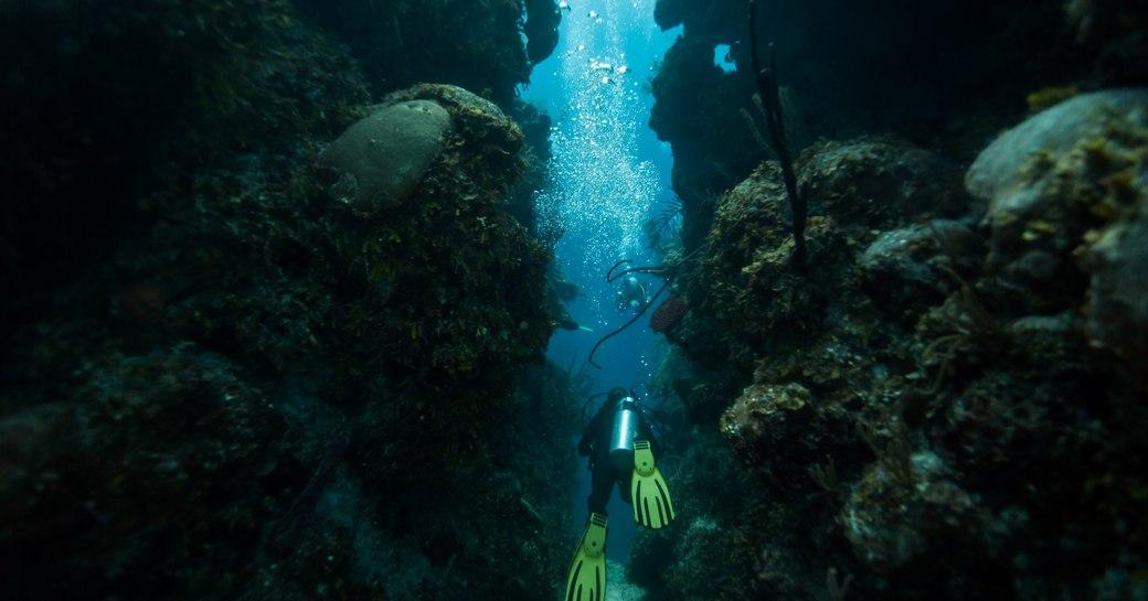 Scuba diver swims through blue hole