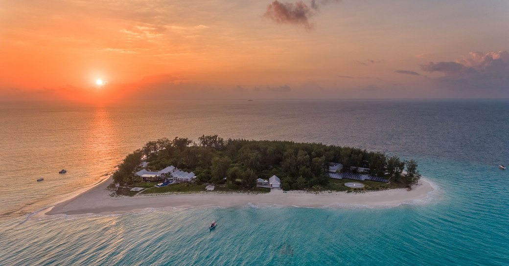 sun setting over thanda island aerial shot